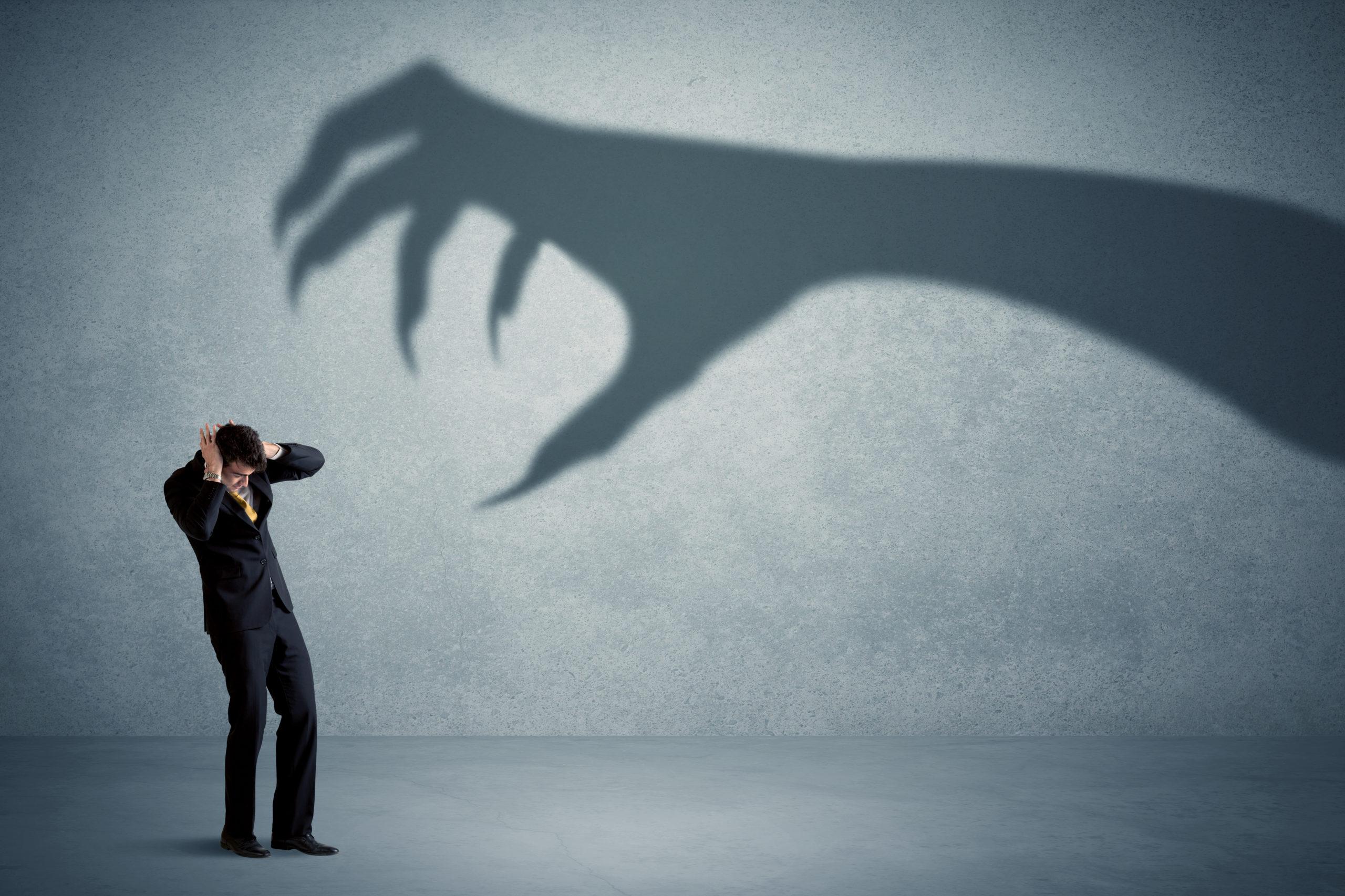 Bild eines Mannes, der Angst hat, vor dem Schatten eine bedrohlichen Hand