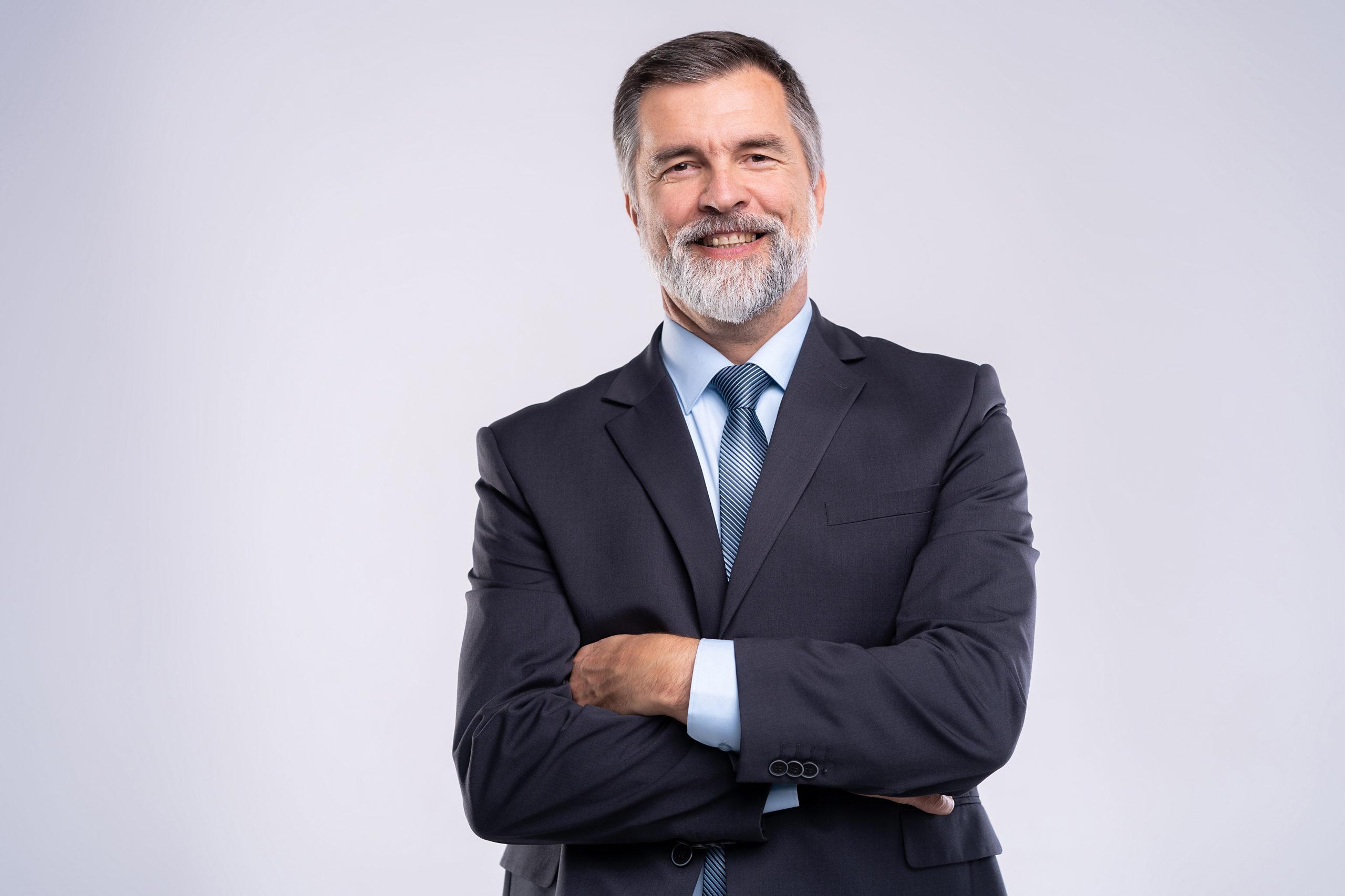 Foto eines Mannes mit grauem Bart im Anzug mit verschränkten Armen
