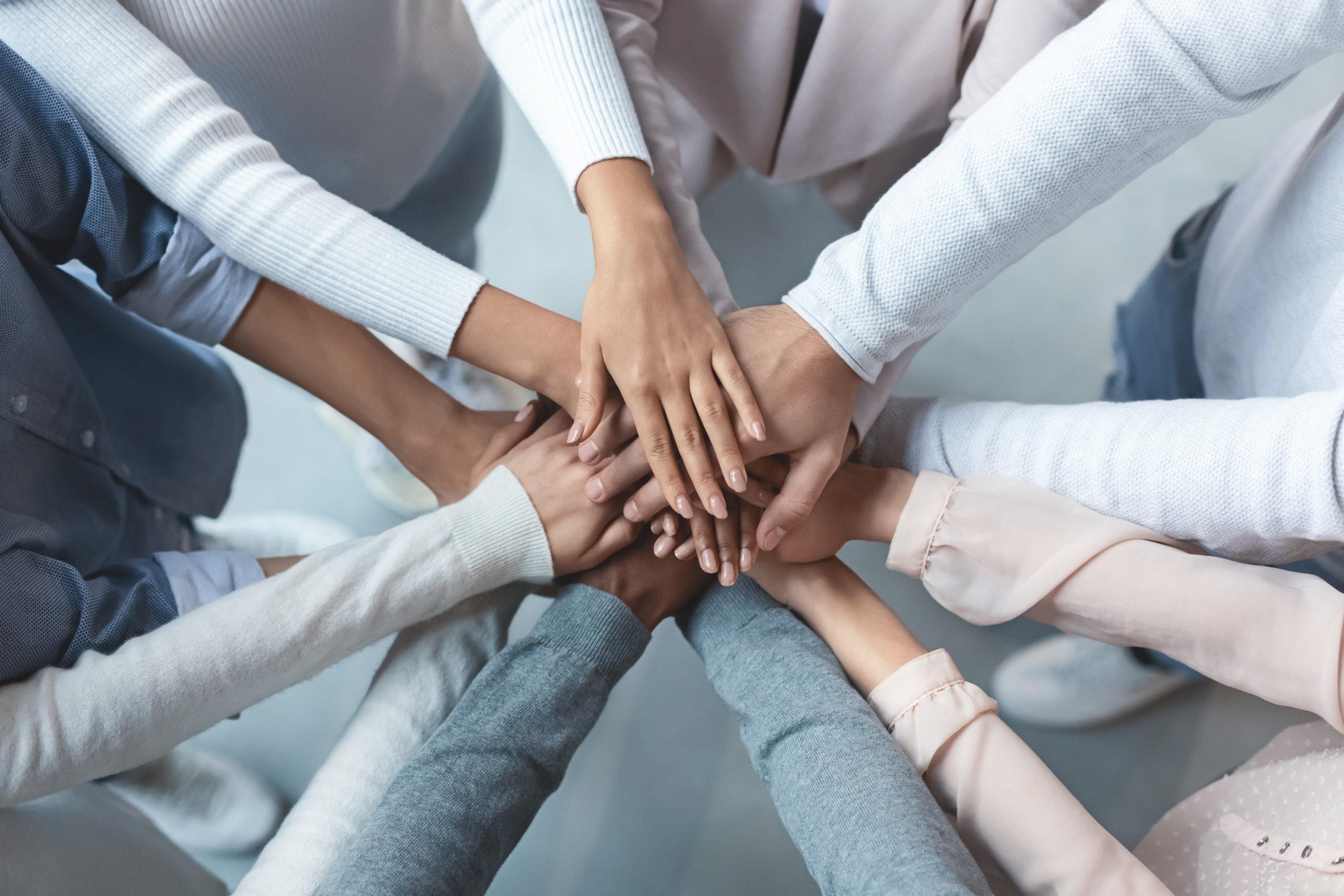 Foto von vielen Armen mit übereinander gelegten Händen