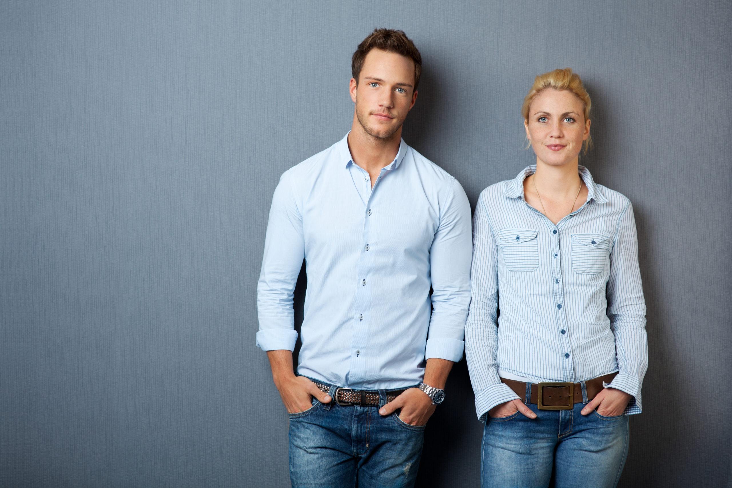 Foto von modernem jungen paar nebeneinander stehend in Jeans mit hellblauem Hemd